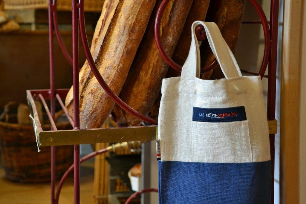 Sac à pain bleu le Craquant accroché dans une boulangerie auprès de baguettes de tradition