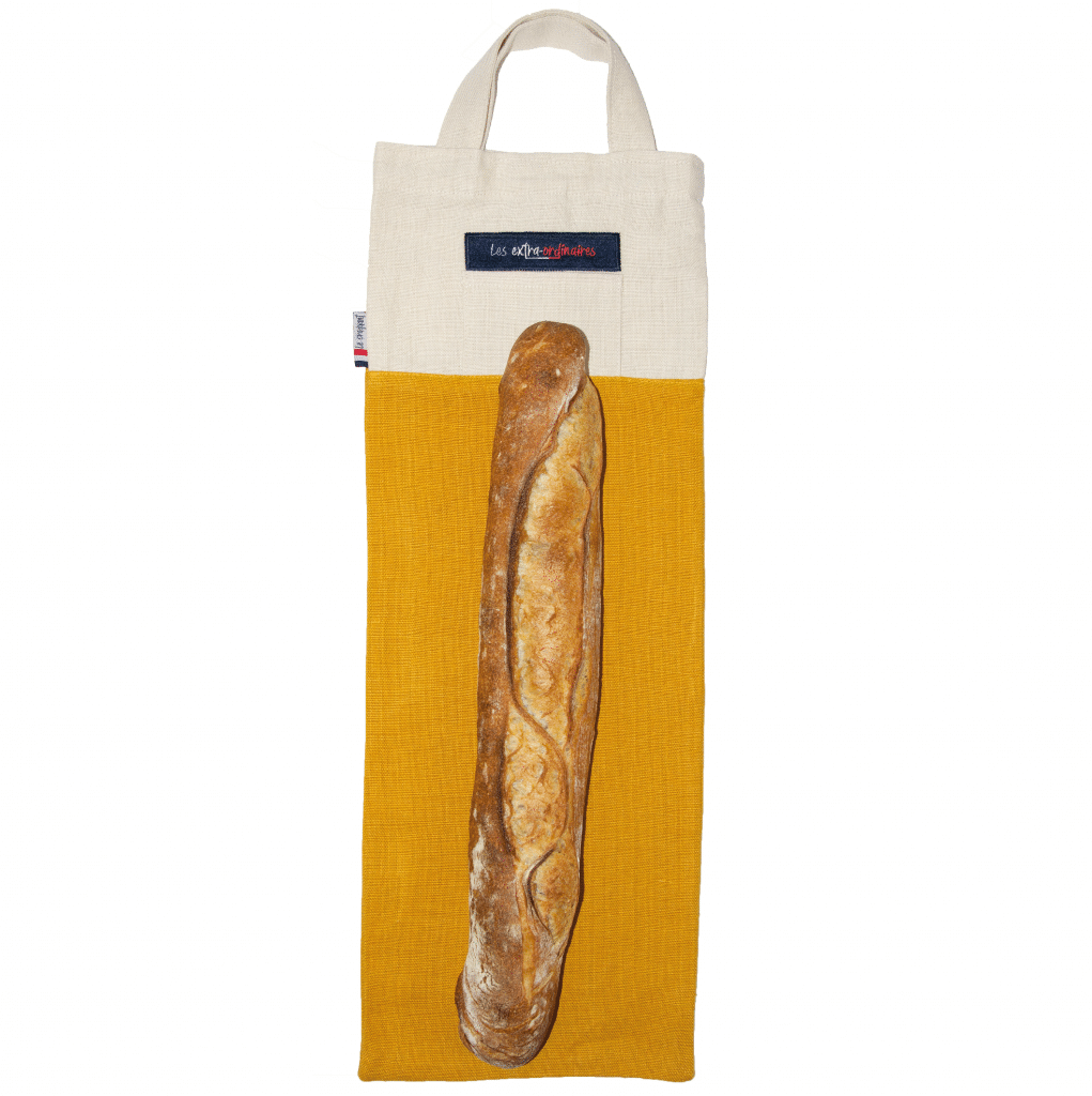 """Sac à pain """"Le Craquant"""" jaune posé à plat avec une baguette tradition dessus"""