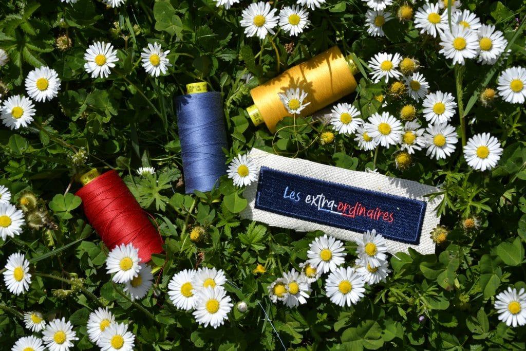 Logo Les extra-ordinaires brodé, posé dans l'herbe près de pâquerettes et entouré de bobines de fil rouge, jaune et bleu